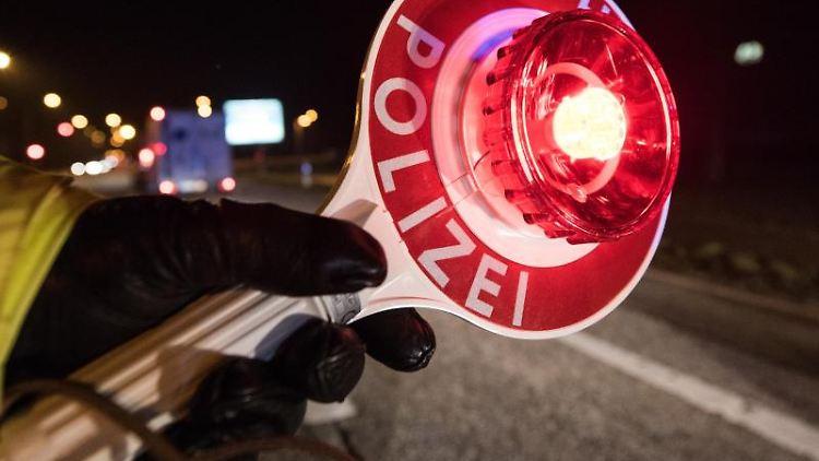 Ein Polizist hält während einer Verkehrskontrolle mit einer Haltekelle Fahrzeuge an. Foto: Patrick Seeger/Archivbild