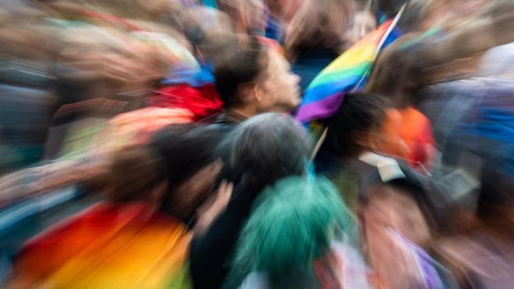 Ein Mann, der an der Christopher-Street-Day-Parade in München, hält eine Regenbogen-Fahne. Foto: Peter Kneffel