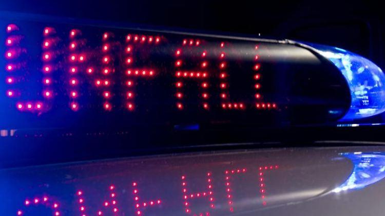 Das Blaulicht auf einem Fahrzeug der Polizei leuchtet, während auf dem Display