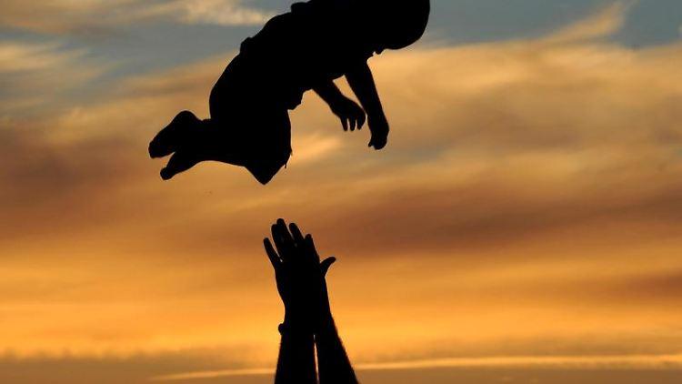 Ein Vater spielt beim Sonnenuntergang mit seinem Sohn. Foto: Julian Stratenschulte/Archiv