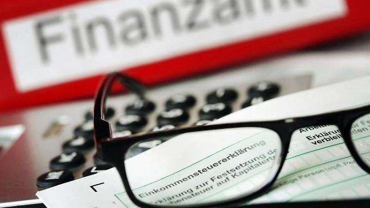 Auf einem Vordruck für die Steuererklärung liegt vor einem Ordner mit dem Aufdruck