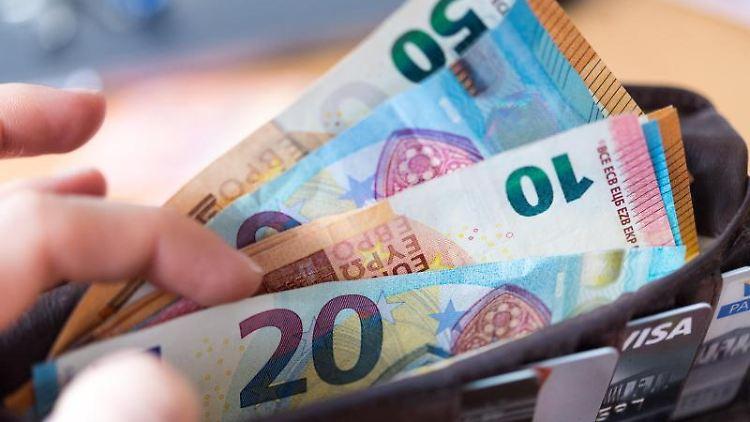 Eine Frau hält eine Geldbörse mit zahlreichen Banknoten und Bankkarten in der Hand. Foto: Monika Skolimowska/Archivbild