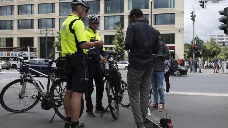 Polizisten der Fahrradstaffel kontrollieren auf einem Bürgersteig zwei Jugendliche mit E-Tretrollern. Foto: Paul Zinken