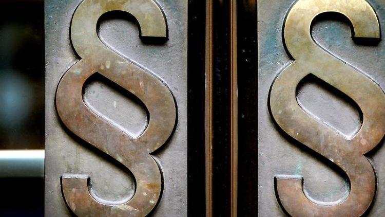 Paragrafen-Symbole sind an Türgriffen angebracht. Foto: Oliver Berg/Archivbild