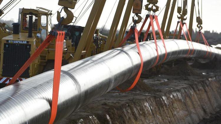 Ein Pipeline-Stück der Erdgaspipeline Eugal wird bei Anklam ins Erdreich verlegt. Foto: Stefan Sauer/Archivbild