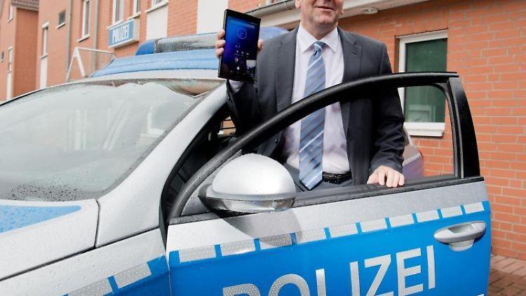 Niedersachsens Innenminister Boris Pistorius (SPD) steht mit einem Tablet-Computer an einem Polizeiwagen. Foto: Julian Stratenschulte/Archiv