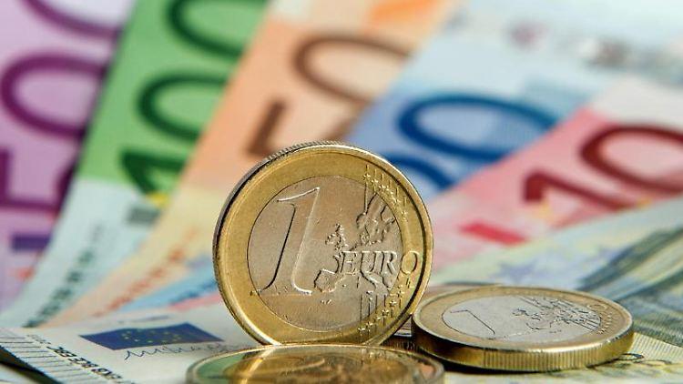 Zahlreiche Euro-Banknoten und Euromünzen. Foto: Daniel Reinhardt/Archivbild