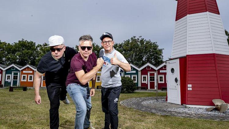 Die Hip-Hop-Band Fettes Brot steht auf der Insel Helgoland neben einem Leuchtturm. Foto:Axel Heimken