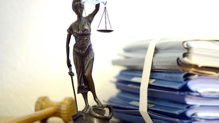Justitia mit Holzhammer und ein Aktenstapel. Foto: Volker Hartmann/Archivbild