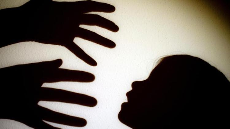 Schatten von Händen einer erwachsenen Person und dem Kopf eines Kindes sind an einer Wand eines Zimmers zu sehen. Foto: Patrick Pleul/Archivbild