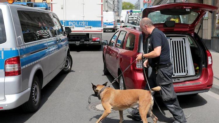 Ein Polizist geht mit einem Sprengstoffspürhund zu einem Wohnhaus. Foto:Oliver Berg