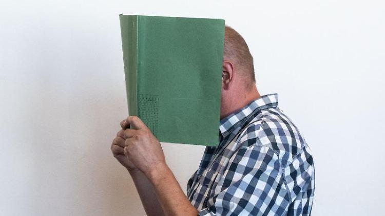 Der Angeklagte Heiko V. verbirgt im Landgericht sein Gesicht hinter einer Aktenmappe. Foto:Bernd Thissen/dpa-POOL/Archivbild