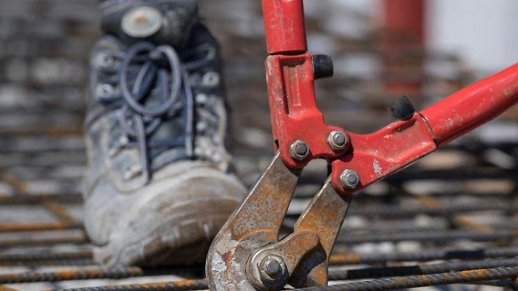 Ein Handwerker auf einer Baustelle. Foto: Boris Roessler/Archivbild