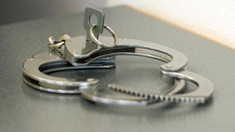 Handschellen liegen auf einem Tisch. Foto: Armin Weigel/Archiv