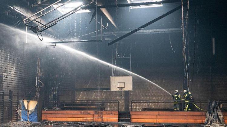Feuerwehrleute löschen den Brand in der Turnhalle einer Bochumer Gesamtschule. Foto: dpa/Feuerwehr Bochum