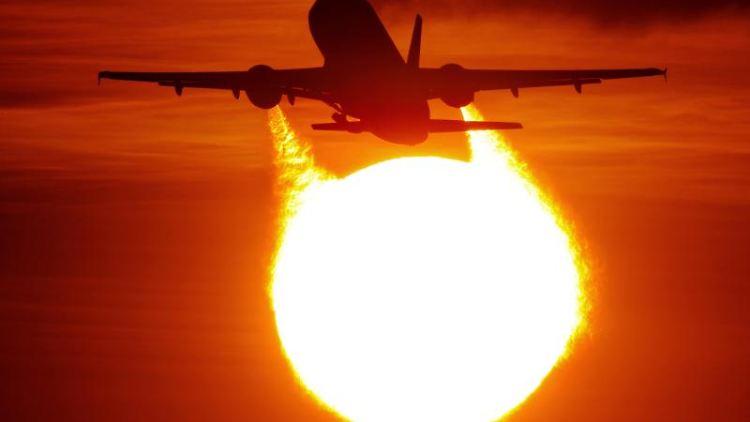 Ein Flugzeug startet am Flughafen vor der untergehenden Sonne. Foto:Julian Stratenschulte