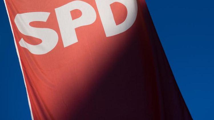 Ein Schatten fällt auf eine Fahne mit dem SPD Logo. Foto: Julian Stratenschulte/Archivbild