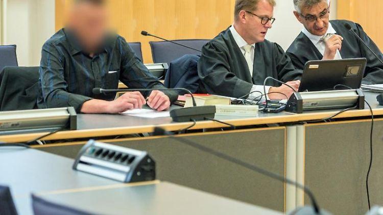 Der wegen Totschlags Angeklagte (l) sitzt im Verhandlungssaal des Landgerichts neben seinen Verteidigern. Foto: Armin Weigel