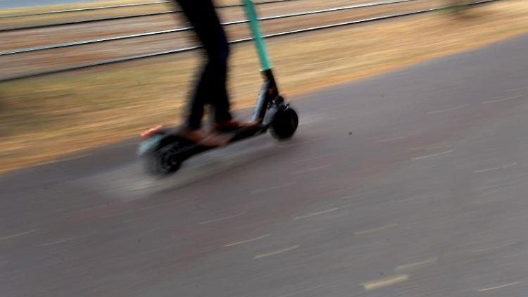 Ein Mann fährt mit einem E-Tretroller auf einem vom Gehweg abgetrennten Radweg durch die Stadt. Foto:Federico Gambarini