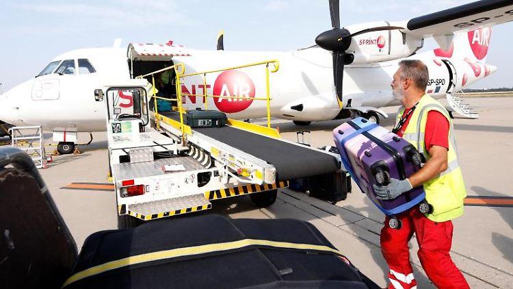 Ein Mitarbeiter legt Koffer auf ein Förderband zum Flugzeug. Foto: Wiese/Flughafen Düsseldorf /dpa