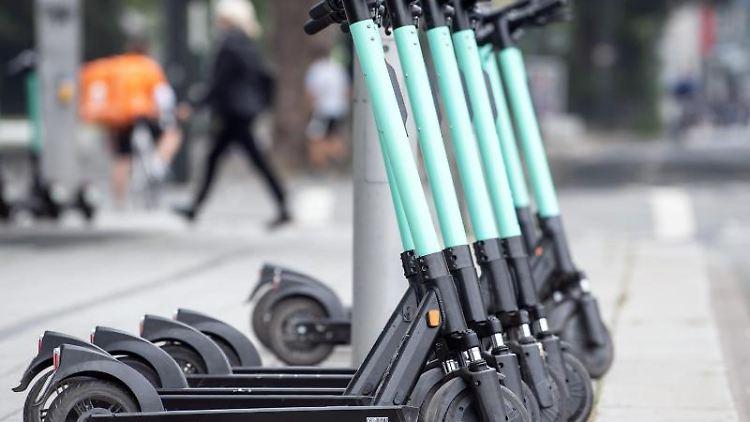 E-Tretroller stehen am Straßenrand und warten auf Kunden. Foto: Federico Gambarini