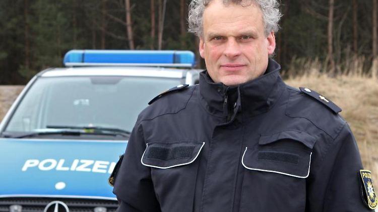 Andreas Schorlemmer steht vor einem Polizeiauto. Foto: Bernd Wüstneck