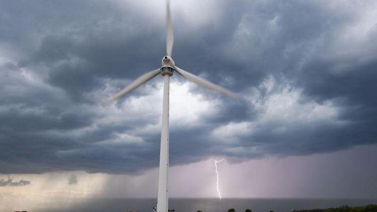 Ein Unwetter zieht nahe Hannover über ein Feld mit einem Windrad hinweg, als am Horizont ein Blitz einschlägt. Foto: Julian Stratenschulte