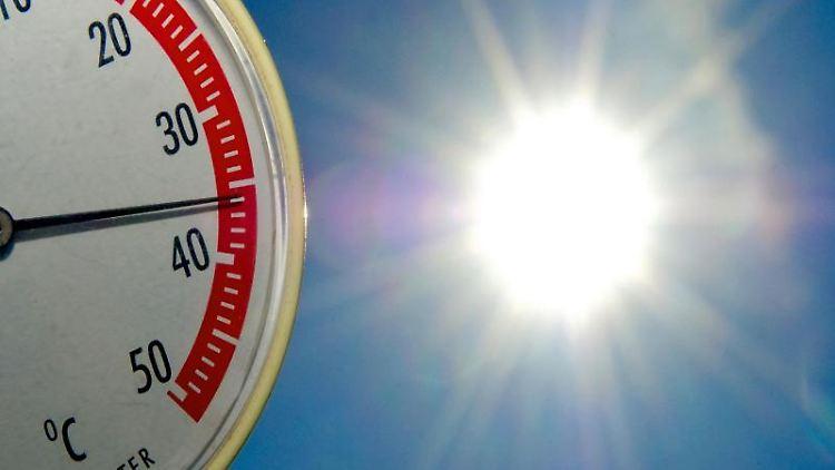 Ein Thermometer zeigt fast 36 Grad Celsius an - im Hintergrund blauer Himmel und Sonne. Foto: Patrick Pleul/Archivbild