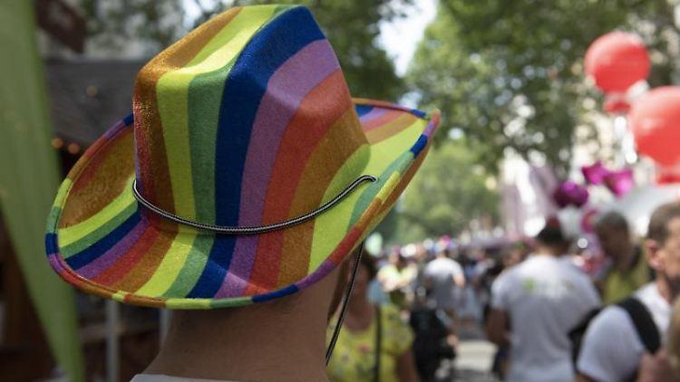 Ein Mann mit einem Hut in den Regenbogenfarben besucht das 27. lesbisch-schwule Stadtfest im Berliner Bezirk Schöneberg. Foto: Paul Zinken