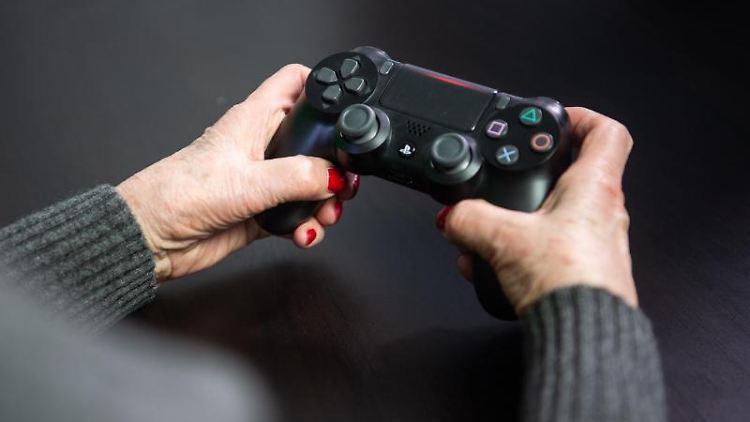 Eine ältere Dame spielt ein Videospiel an der Playstation 4. Foto: Arne Immanuel Bänsch/Archivbild