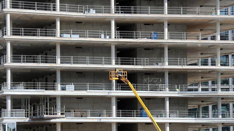Arbeiter montieren von einer Hebebühne aus Teile an einem Neubau. Foto:Jens Büttner/Archiv