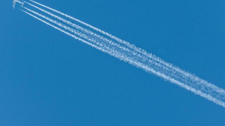 Ein Passagierflugzeug zieht Kondensstreifen hinter sich her. Foto: Robert Michael/Archivbild