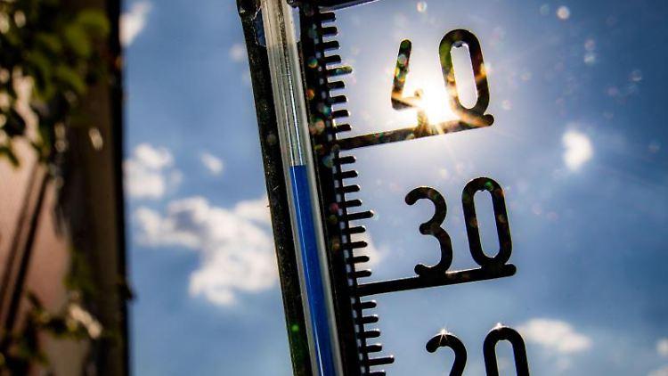 Ein Thermometer an einer Hauswand klettert am Nachmittag in Richtung der 40-Grad-Marke. Foto:Frank Rumpenhorst/Archivbild