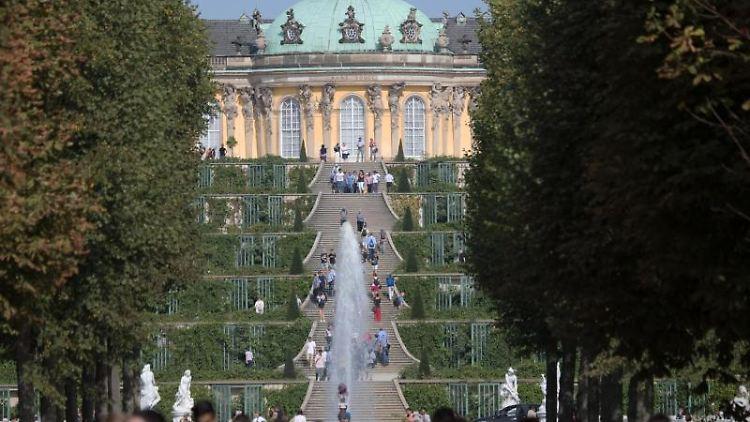 Touristen laufen bei sommerlichem Wetter durch den Schlosspark Sanssouci in Potsdam. Foto: Ralf Hirschberger7Archiv