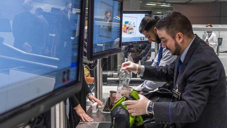 Mitarbeiter der Flughafen-Sicherheit durchsuchen bei der Vorstellung neuer Passagier-Kontrollspuren Gepäck. Foto: Boris Roessler/Archivbild