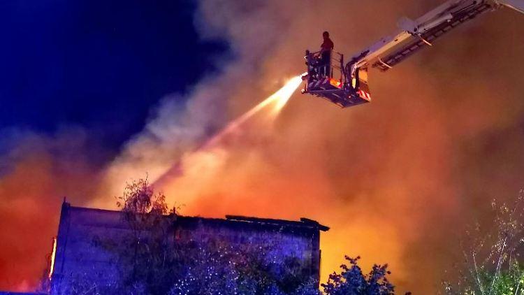 Feuerwehrleute sind bei einem Brand von Scheunen im Einsatz. Foto: Julian Stähle