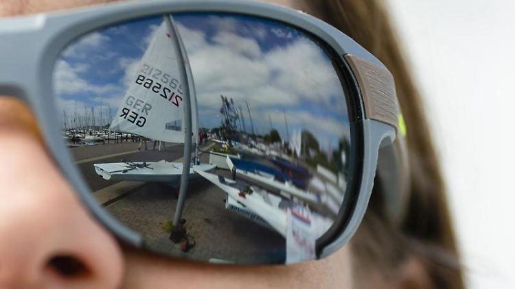 Das Segel eines Bootes spiegelt sich in der Sonnenbrille einer Frau. Foto: Frank Molter/Archiv