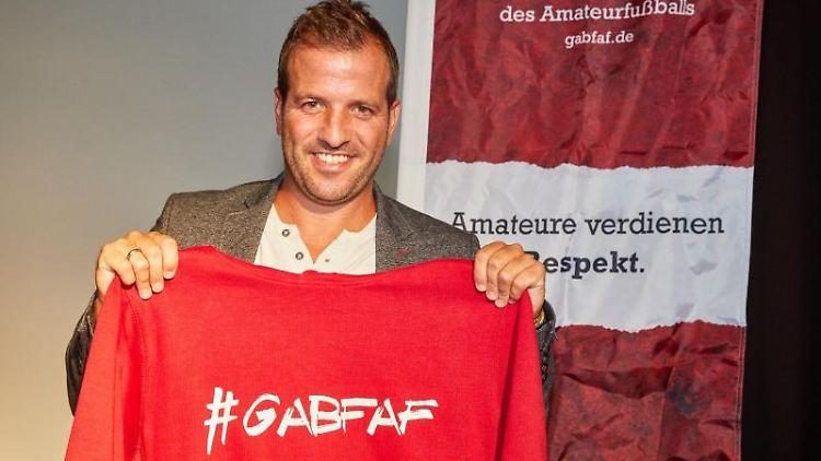 Rafael van der Vaart, Ex-HSV-Profi, hält einen Kapuzenpullover. Foto: Georg Wendt/Archiv