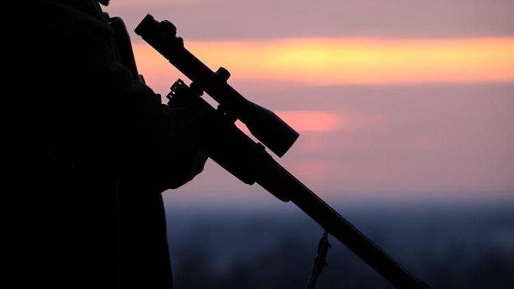 Ein Jäger hält sein Gewehr in der Abenddämmerung. Foto: Friso Gentsch/Archiv
