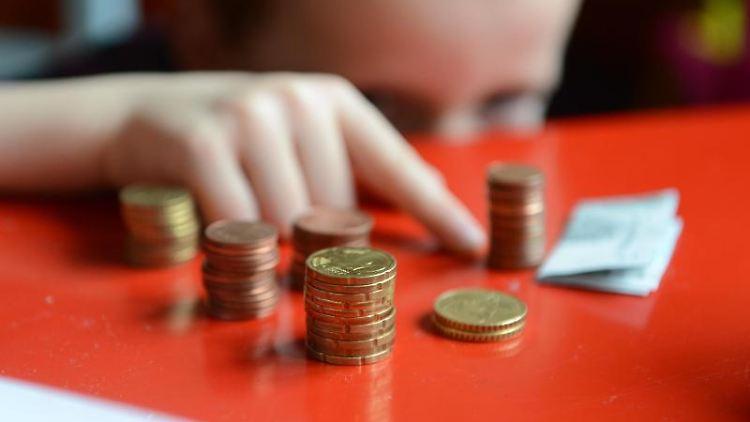 Ein Junge zählt sein gespartes Taschengeld. Foto: Jens Kalaene/Archivbild