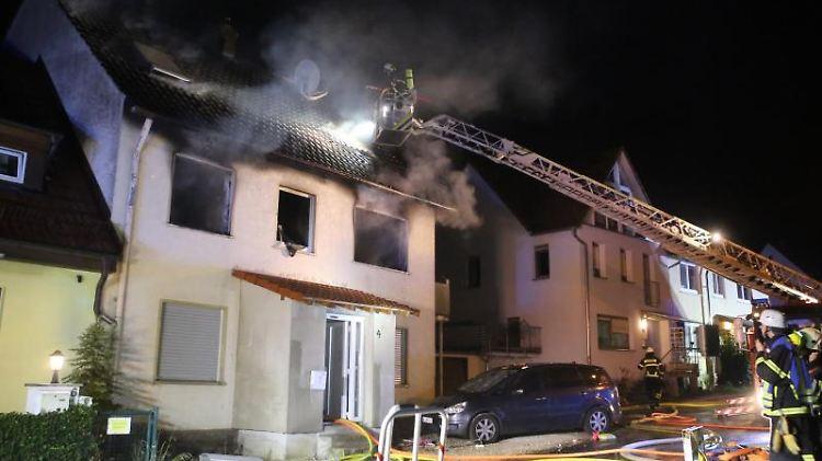 Feuerwehrleute löschen einen Brand in einem Wohnhaus. Foto: Ralf Zwiebler