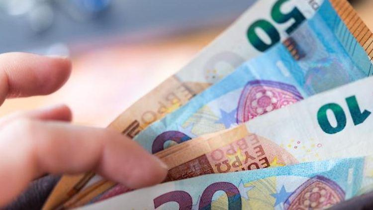 Eine Person hält eine Geldbörse mit zahlreichen Banknoten in der Hand. Foto: Monika Skolimowska/Archivbild