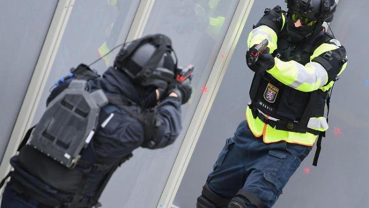 Zwei Polizeibeamte präsentieren im Rahmen einer Anti-Terror-Übung eine mobile Übungsörtlichkeit für Farb- und Lasertraining. Foto: Arne Dedert