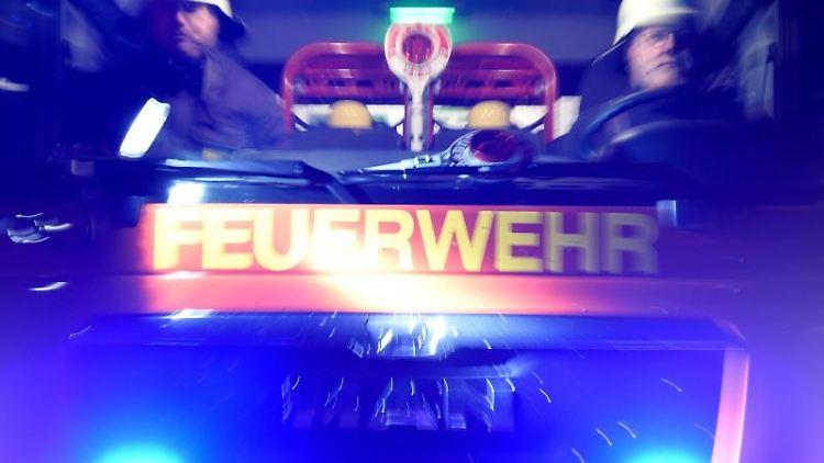 Feuerwehrmänner in einem Löschfahrzeug. Foto: Carsten Rehder/Archivbild