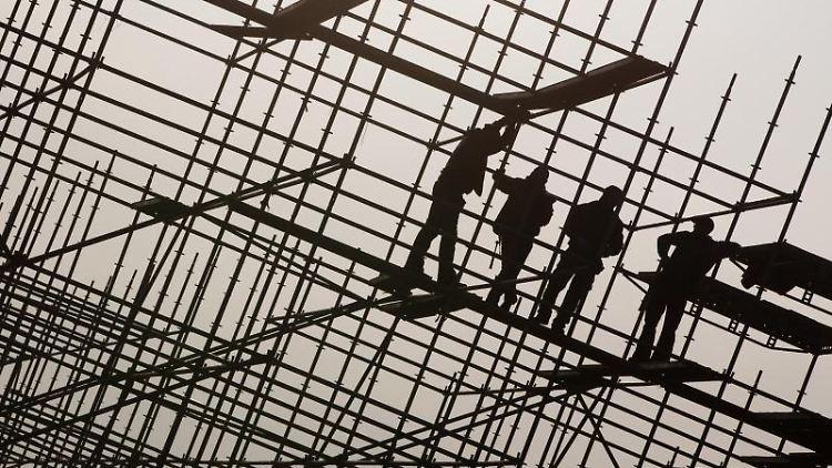 Gerüstbauer errichten auf einer Brückenbaustelle ein Gerüst. Foto: Christian Charisius/Archivbild