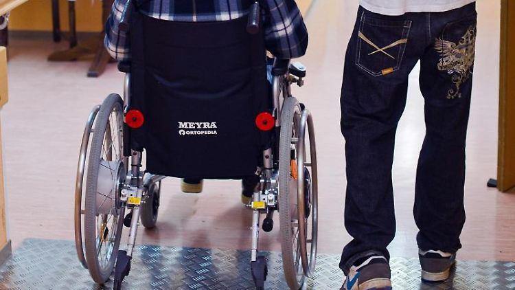 In einem Seniorenheim betreut ein Mann einen Senioren. Foto: Patrick Pleul/Archivbild