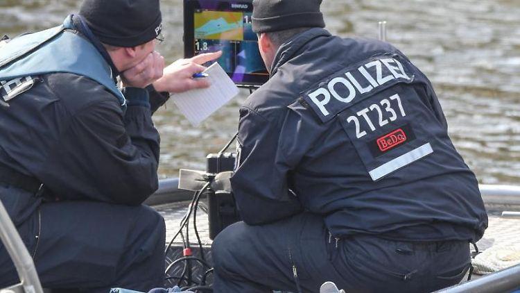 Polizeibeamte schauen auf einem Plotter auf ein Echolot bei der Suche nach der vermissten Rebecca am Storkower Kanal. Foto: Patrick Pleul/Archivbild