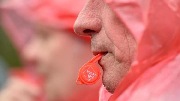 Ein Mann hat bei einer Kundgebung eine Trillerpfeife mit dem IG Metall Logo im Mund. Foto: Caroline Seidel/Archiv