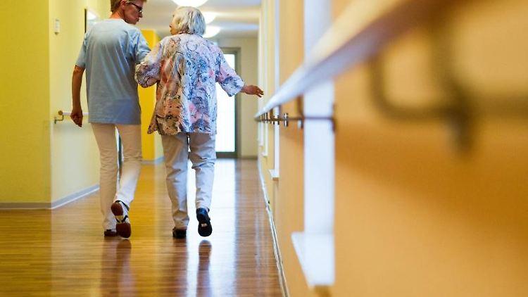 Eine Pflegekraft geht in einem Pflegeheim mit einer älteren Dame über einen Korridor. Foto: Christoph Schmidt/Archivbild