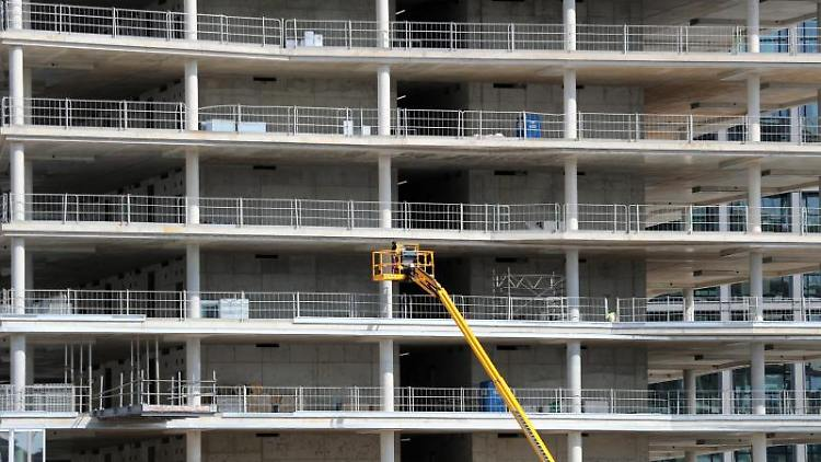 Arbeiter montieren von einer Hebebühne aus Teile an einem Neubau. Foto: Jens Büttner/Archivbild